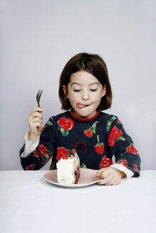 Portrait of a girl (8-9) eating piece of cake - PMF00571