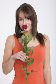 Young woman sniffing at rose, portrait - RDF00878