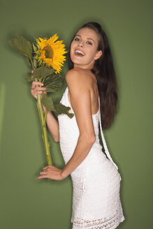 Young woman holding a sunflower, portrait - RDF00768
