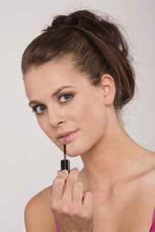 Young woman using a lipstick, portrait - RDF00735