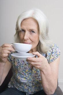 Senior woman drinking coffee, portrait - WESTF08383