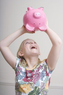 Girl (8-9) with piggy bank, portrait - WESTF08350