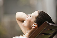 Young woman in deck chair listening to MP3-Player, portrait - ABF00361