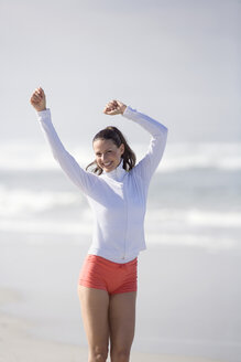 Young woman on beach, arms up - ABF00340