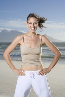 South Africa, Cape Town, Young woman exercising on beach, portrait - ABF00277