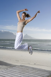 South Africa, Cape Town, Young woman jumping on beach - ABF00274