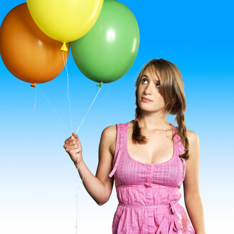 Teenage girl (16-17)  holding bunch of balloons, portrait - JLF00303