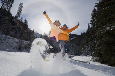 'Austria, Salzburger Land, Young couple jumping in snow - HH02527