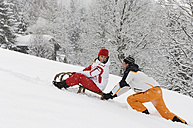 Austria, Salzburger Land, Altenmarkt-Zauchensee, Young couple, woman sitting on sledge - HH02541