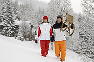 Austria, Salzburger Land, Altenmarkt-Zauchensee, Young couple, man carrying sledge - HH02538