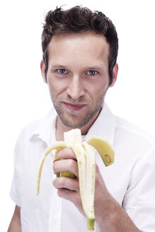 Portrait of a young man holding a banana, close-up - BMF00348