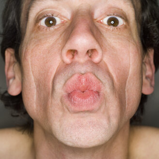 Man pursing lips, portrait, close-up - MUF00564