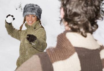 Austria, Salzburger Land, Altenmarkt, Young couple having snowball fight - HH02609