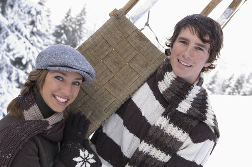 Austria, Salzburger Land, Altenmarkt, Young couple in snowscape, carrying sled - HH02594