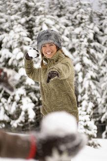 Austria, Salzburger Land, Altenmarkt, snowball fight, woman throwing a snowball - HH02582