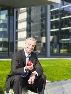 Germany, Baden-Württemberg, Stuttgart, Businessman holding an apple - WEST08580