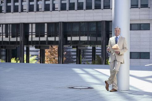 Germany, Baden Württemberg, Stuttgart,  Businessman holding newspaper, smiling - WEST08528