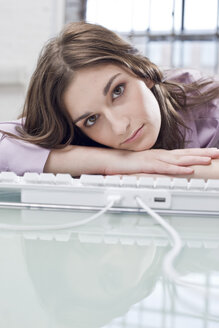 Young businesswoman office, head resting on keypad - BMF00371