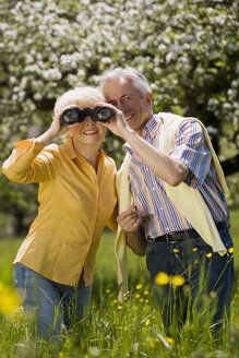 Germany, Baden Württemberg, Tübingen, Senior couple, senior woman looking through binoculars - WESTF08909