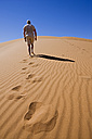 Africa, Namibia, Namib desert, Man walking over sand dune, rear view - FOF00967
