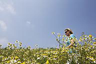 Woman walking across camomile field - GWF00810