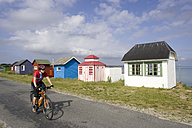 Denmark, Woman mountain biking alongside frame houses - DSF00187