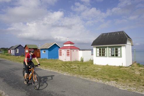 Denmark, Woman mountain biking alongside frame houses - DSF00187