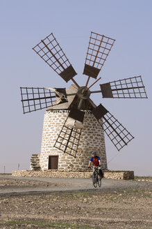 Spain, The Canary Islands, Man mountain biking, windmill in background - DSF00169