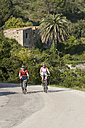 Italy, Tuscany, Capoliveri, Mountainbikers riding across country road - DSF00163