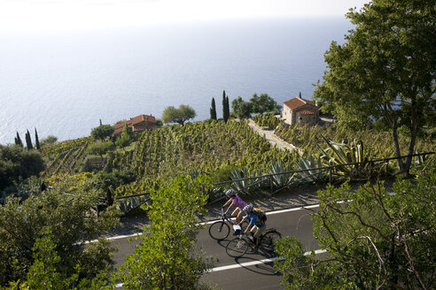Italy, Tuscany, Elba, Mountainbikers riding on coastal highway - DSF00154