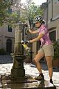 Italy, Tuscany, Elba, Poggio, Female mountainbiker filling water bottle - DSF00151