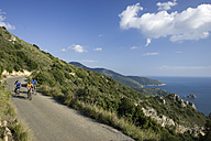 Italy, Tuscany, Monte Argentario, Mountainbikers on seaside highway - DSF00145