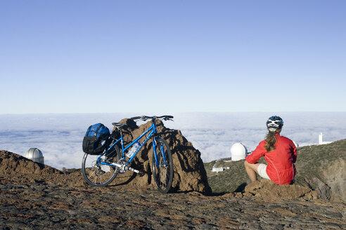 Spain, The Canary Islands, La Palma, Woman with mountain bike taking a break, looking over clouds - DSF00127