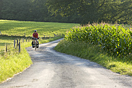 Germany, Bavaria, Oberland, Man mountain biking across farm track - DSF00112