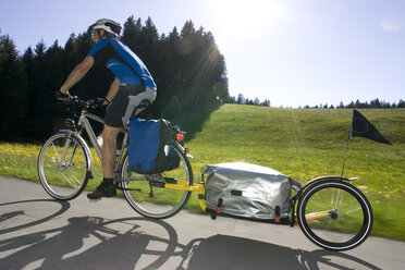 Germany, Bavaria, Man riding mountainbike with trailer - DSF00106