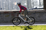 Italy, Trento, Riva del Garda, Female mountainbiker riding across pier - DSF00088