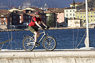Italy, Trento, Torbino, Man mountain biking across pier - DSF00073