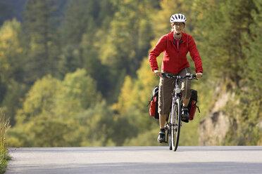 Austria, Tyrol, Ahornboden, Mountainbiker riding across highway - DSF00067