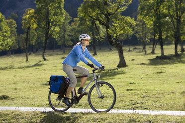Austria, Tyrol, Ahornboden, Woman mountain biking, trees in background - DSF00064