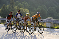 Germany, Bavaria, Sylvenstein, Four mountain bikers riding across highway - DSF00058