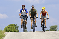 Germany, Bavaria, Oberland, Three mountain bikers riding across highway - DSF00055