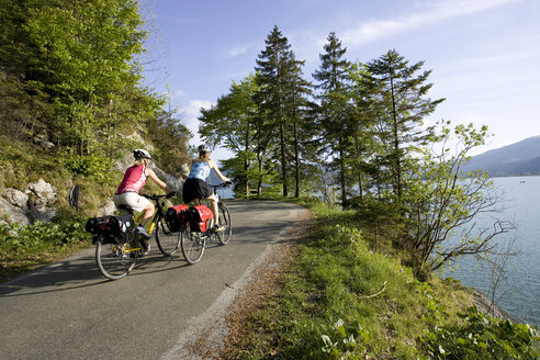 Germany, Bavaria, Walchensee, Two women mountain biking alongside lake, rear view - DSF00046