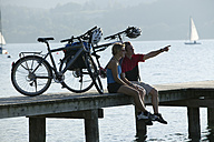 Germany, Bavaria, Couple with mountain bikes taking a break on landing stage - DSF00016
