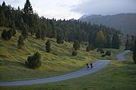 Germany, Bavaria, Mittenwald, Couple mountain biking across highway - DSF00010