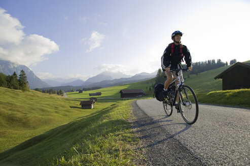 Germany, Bavaria, Mittenwald, Woman mountain biking across highway - DSF00007