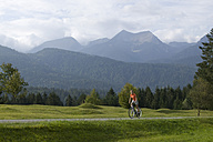 Germany, Bavaria, Mittenwald, Woman mountain biking against mountain scenery - DSF00001