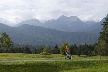 Germany, Bavaria, Mittenwald, Woman mountain biking against mountain scenery - DSF00001