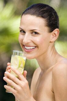 Young woman in bikini holding lemon drink - ABF00438