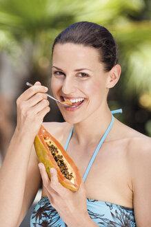 Young woman in bikini spooning a pawpaw - ABF00432