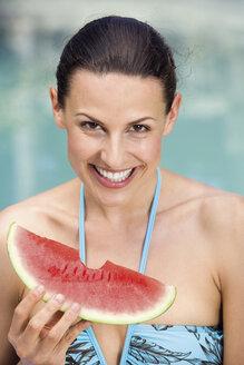 Young woman in bikini holding melon, portrait, close-up - ABF00428